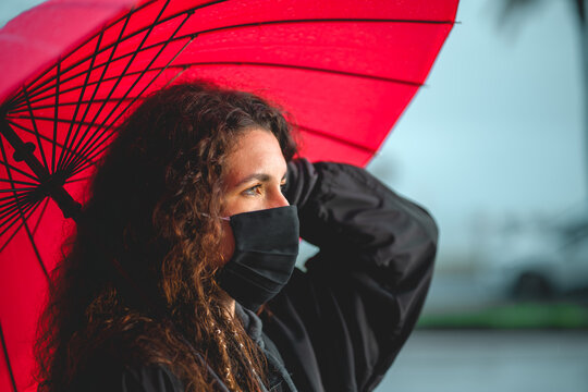 Portrait of a curly woman holding a red umbrella in Palma, Spain