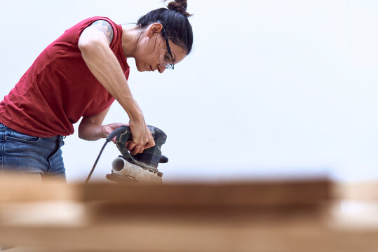 Young woman polishing a wooden plank with a power sander