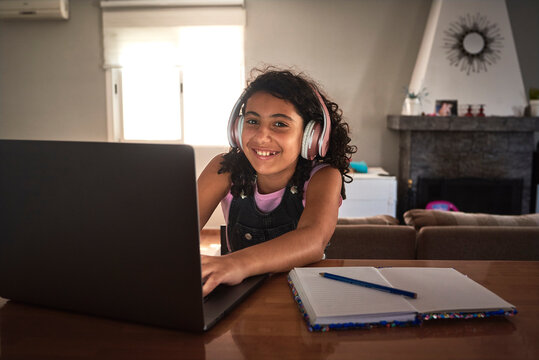 a girl smiling as she studies with her laptop from home