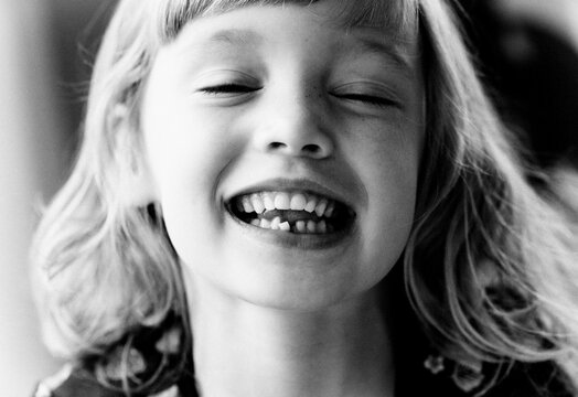 portrait of a young girl showing her wobbly tooth smiling