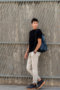 Young student with backpack leaning on wall, looking away