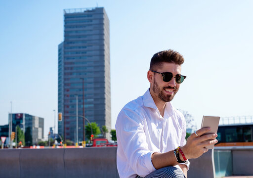 Young bearded man sits on bench outdoor against modern glass building