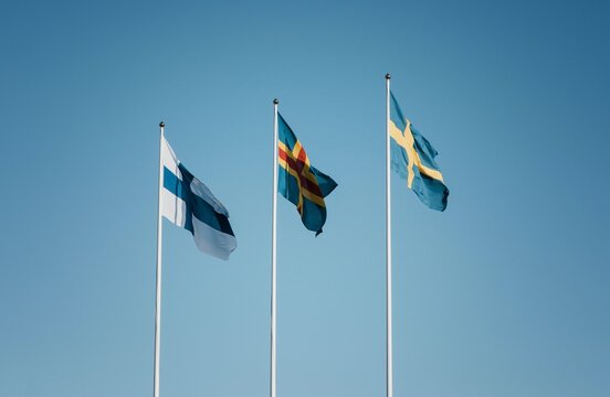 3 skandinavian flags flying together against a blue sky in Finland