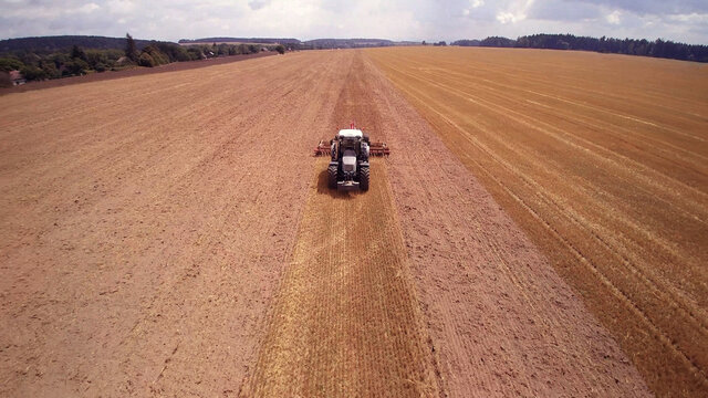 agricultural tractor with plows. while plowing large field.