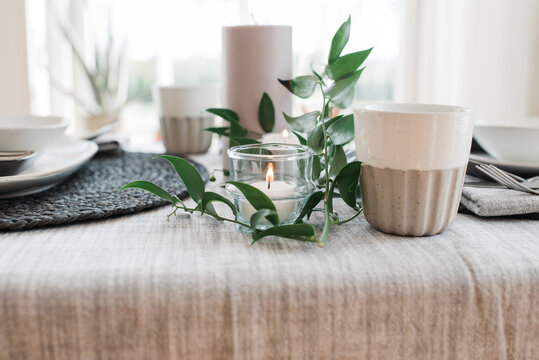 candle and plants on a dinner table for two
