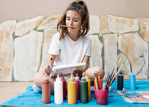 white girl biting a painting brush while painting with her finger her picture siting on a terrace in front of bottle paintings. Horizontal photo