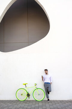 Young bearded man leaning against a white wall using the mobile phone