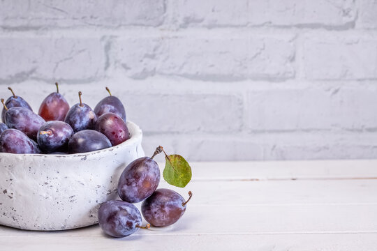 Fresh plum fruit in bowl on white rustic background. with copyspace.