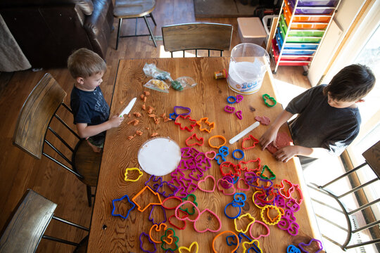 Overhead view of siblings paying with clay and cookie cutters