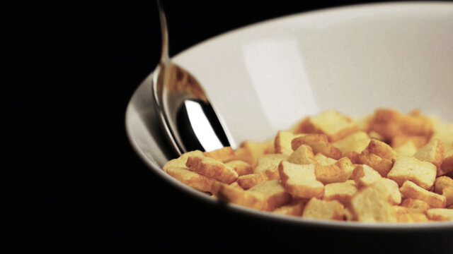 close up on corn flakes in bowl with spoon in black background.