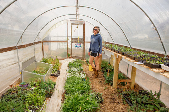 A woman in cowboy boots stands in a greenhouse full of plant seedlings
