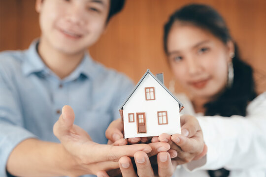 Young couple showing house model.