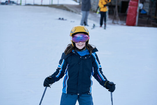 girl with helmet and glasses looks smiling on a ski slope