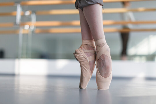 female feet in pointe shoes standing on point, horizontal shot