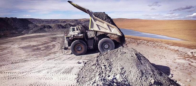Haul truck unloading soil in quarry