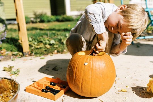 Child carving out pumpkins for halloween on their patio