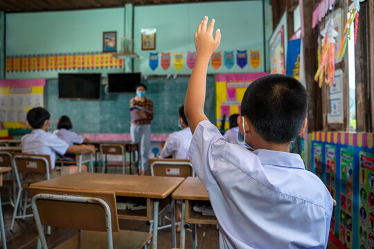 Asian student with hands up during learning in classroom at elem