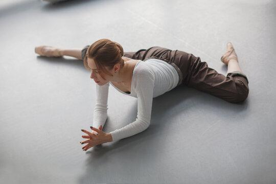 female ballet dancer stretching in studio