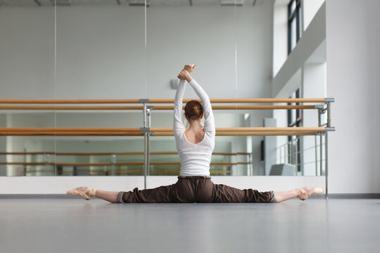 female ballet dancer stretching legs near mirror in dance studio
