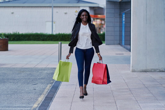 Young black woman walking down the street with red, yellow and b