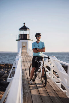 male cyclist poses with bike in front of lighthouse on Maine coast