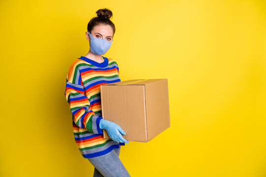 Profile photo of brunette girl hold huge box wear blue mask gloves from corona rainbow sweater pants isolated on bright yellow background