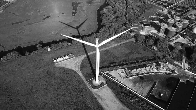 Wind turbine against Industrial district, clean energy production, aerial view black and white