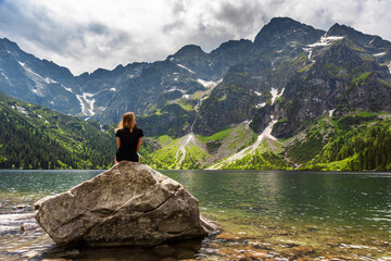 summer in the Polish High Tatras with a tourist girl walking near the mountain lakes.