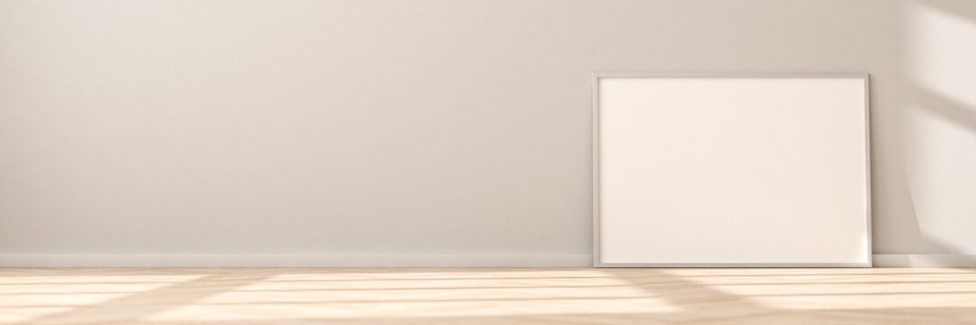 Horizontal empty Picture Frame on parquet floor leaning against bright wall. Sunlight flooding in from the left. Web banner size with plenty of additional copy space.