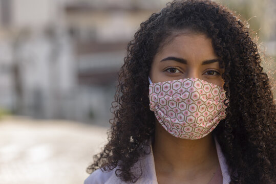 Black woman with facemask on urban background