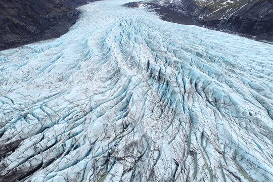 Beautiful glaciers flow through the mountains in Iceland. Aerial view and top view.