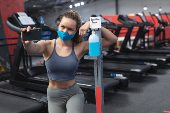 Fit caucasian woman wearing face mask taking a selfie with sanitizer foot dispenser stand with sanit
