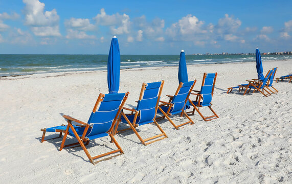 Blue beach chairs and umbrellas facing the Gulf of Mexico on a beautiful day in Fort Myers Beach, Florida, USA.