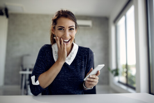 Happy businesswoman reading text message in disbelief in the office.