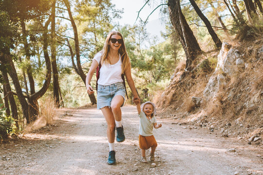 Mother with child daughter walking in forest family vacation mom travel with baby hiking together active healthy lifestyle outdoor happy emotions