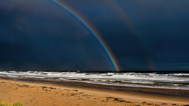 Torrential rain sweeping along the shores of a stormy beach with a double rainbow in a dark sky