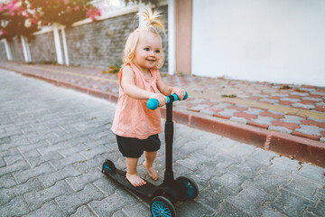 Baby girl riding scooter in city happy child 1 year old healthy lifestyle family fun activity...