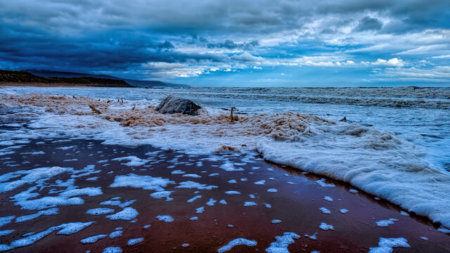 Stormy seas and foam washing up on Brora beach in the Highlands