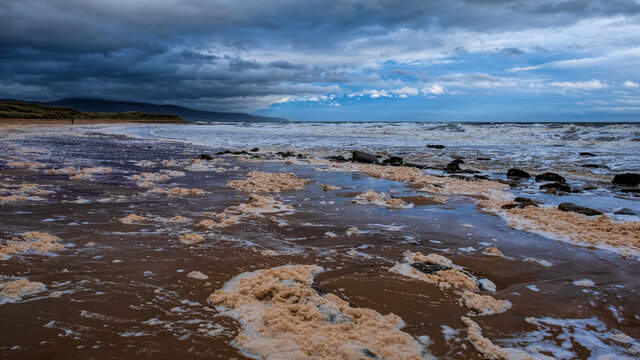 Lone walker on Brora beach in the Highlands on a stormy day