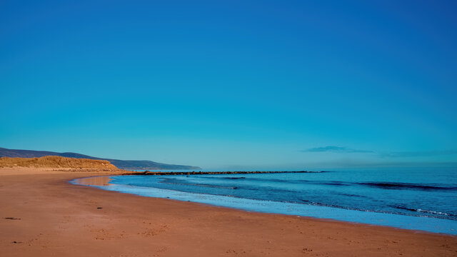 Brora beach in Sutherland in the Highlands of Scotland on a clear sunny day with blue skies and blue water