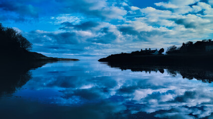 Sky and clouds reflected in the mirror calm waters of River Brora at high tide