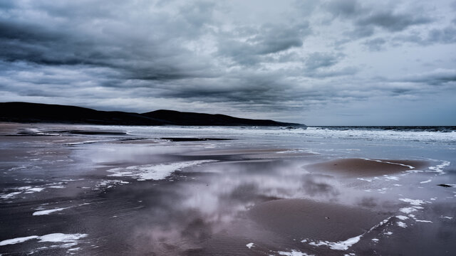 Stormy seas, surf, and grey clouds reflected in wet sand on Brora beach