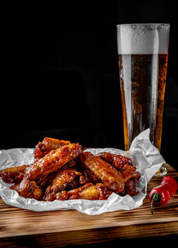 glass of fresh beer and fried chicken wings on wooden table on black background