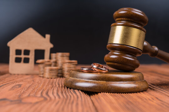 Divorce property division concept. Judge hammer, home and coin money. Court law