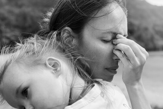 Stressed out sad mother holding her baby. Postpartum depression.