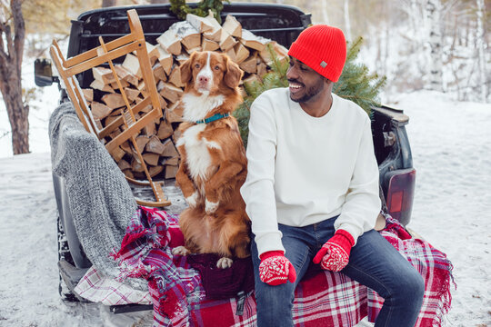 African American man sits with a dog in the trunk of a car in the winter forest. A man in a white sweatshirt.