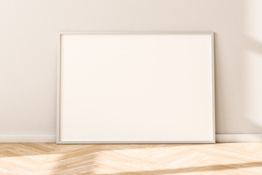 Horizontal empty Picture Frame on parquet floor leaning against bright wall. Sunlight flooding in from the left.