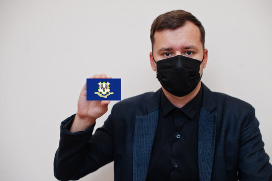 Man wear black formal and protect face mask, hold Connecticut flag card isolated on white background. USA coronavirus Covid country concept.