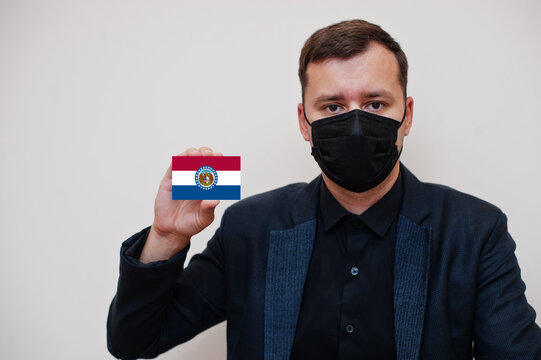 Man wear black formal and protect face mask, hold Missouri flag card isolated on white background. USA coronavirus Covid country concept.