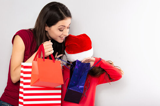 Happy laughing excited mother with open mouth hugging with love her cute joying daughter in santa clause hat looking into Christmas bright color present packages. Portrait